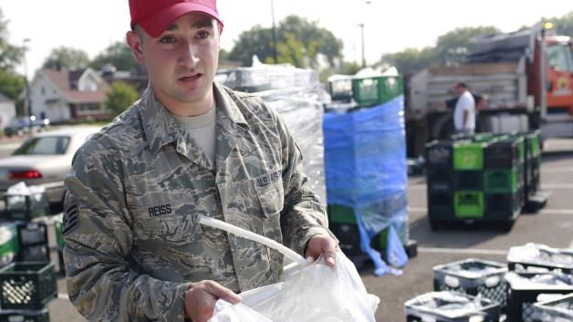 A member of the Ohio Air National Guard carries a bag of safe water.